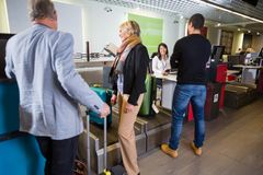 Airline Passengers Weighting Their Luggage At Airport Royalty Free Stock Image