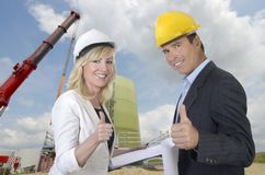Male and female architect and construction site. Smiling and thumb up, outdoor Royalty Free Stock Images