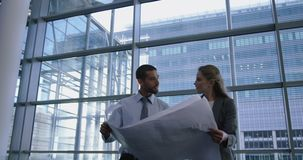 Male and female architects discussing over blueprint in office 4k. Low angle view of male and female architects discussing over blueprint in office. Male stock video