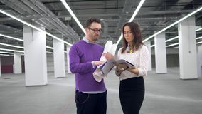 Male and female architects are talking about a project stock footage