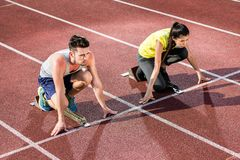 Male and female athlete in starting position at starting block. Of cinder track Stock Images