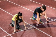 Male and female athlete in starting position at starting block. Of cinder track Royalty Free Stock Photos