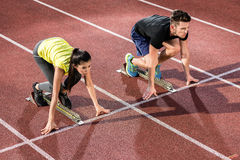 Male and female athlete in starting position at starting block o Stock Photos