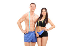 Male and female athletes with measuring tapes Stock Photo