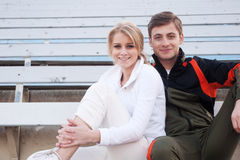 Male and female athletes sitting in the bleachers Royalty Free Stock Photo