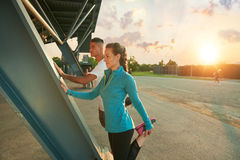 Male and female athletes stretching before going jogging outdoors Stock Image