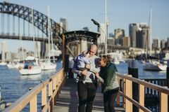 Male and Female With Baby Walking on Wooden Dock stock photography