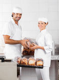 Male And Female Baker's Packing Bread Loaves Royalty Free Stock Photos