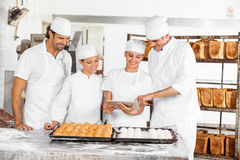 Male And Female Baker's Using Digital Tablet In Bakery Stock Images