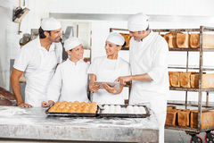 Male And Female Baker's Using Digital Tablet At Table Stock Photo