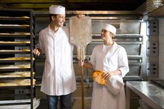 Male and female bakers smiling at each other Stock Image
