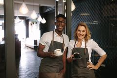 Café owners at their coffee shop holding coffee cups. Male and female barista standing at the entrance of coffee shop holding coffee cups. Happy coffee Royalty Free Stock Image