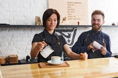 Male and female bartenders brewing fresh coffee at cafe interior. Coffee business backgroung with copy space. Portrait of two young bartenders preparing fresh Stock Photography