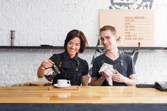 Male and female bartenders brewing fresh coffee at cafe interior. Coffee business backgroung with copy space. Portrait of two young smiling bartenders preparing Stock Images