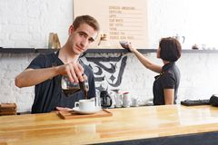 Male and female bartenders brewing fresh coffee at cafe interior. Coffee business backgroung with copy space. Portrait of two young bartenders preparing fresh Stock Photo