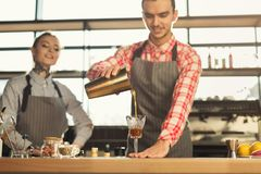 Male and female bartenders brewing fresh coffee at cafe interior. Portrait of two young bartenders preparing fresh bracing drink at coffee house interior Stock Image