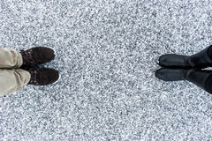 Male and Female boots standing on asphalt covered gritty snow surface. Rough snowy . Textplace. Cold Winter. Top view. Royalty Free Stock Photo
