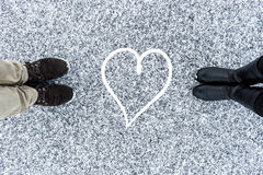 Male and Female boots standing at heart symbol on asphalt covered gritty snow surface. Rough snowy. Cold Winter. Top Royalty Free Stock Image