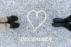 Male and Female boots standing at heart symbol with text december on asphalt covered gritty snow surface. Rough snowy. Male and Female boots standing on asphalt Royalty Free Stock Photos
