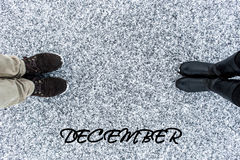 Male and Female boots standing at heart symbol with text december on asphalt covered gritty snow surface. Rough snowy. Winter love. Top view. Relations concept Stock Photography