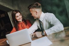 Male and female business coleagues work on project. Concept of successful work process. Portrait of handsome young businessman and his female partner discussing stock photo