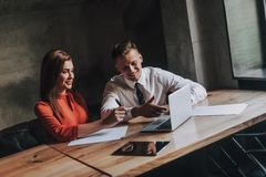Male and female business coleagues work together. Concept of successful work process. Portrait of handsome young businessman and his female partner discussing royalty free stock photo