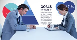 Male and female business colleagues against graphics. Digital composite of Male and female business colleagues against graphics Royalty Free Stock Photography