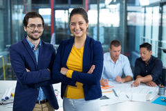 Male and female business executive smiling while colleague interacting over blueprint in background. At office Stock Image