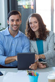 Male and female business executive using digital tablet. In office Stock Photos