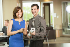 Male and female business partners in break room. Horizontal, color image of a hispanic female and male business partners and management team holding blue prints stock photo