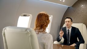 Male and female business partners having negotiations in luxury jet. Woman with red hair and man in black suit with mobile phone in his hand sitting on stock video footage