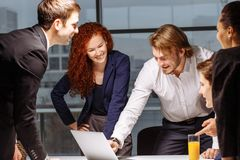 Male and female business people around laptop computer in office. Group of happy diverse male and female business people in formal gathered around laptop Royalty Free Stock Photo