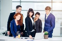 Male and female business people around laptop computer in office. Group of happy diverse male and female business people in formal gathered around laptop Stock Photography