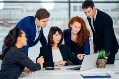Male and female business people around laptop computer in office. Group of happy diverse male and female business people in formal gathered around laptop Royalty Free Stock Image
