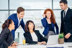 Male and female business people around laptop computer in office. Group of happy diverse male and female business people in formal gathered around laptop Stock Images