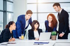 Male and female business people around laptop computer in office. Group of happy diverse male and female business people in formal gathered around laptop Stock Image