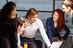 Male and female business people around laptop computer in office. Group of happy diverse male and female business people in formal gathered around laptop Royalty Free Stock Images