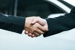 Male and female businessmen shaking hands. After signing the contract. The backdrop is a car Royalty Free Stock Images