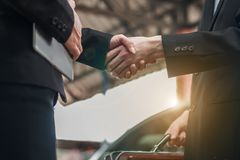 Male and female businessmen shaking hands. After signing the contract. The backdrop is a car Stock Images