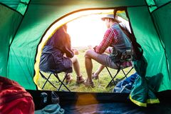 Male and female campers talking each others in front of camping. Tent. People and lifestyles concept. Picnic and travel concept. Nature in summer theme. Back royalty free stock photos