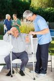 Male And Female Caretakers Helping Senior People Royalty Free Stock Photography