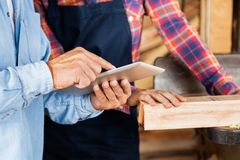 Male And Female Carpenters Using Digital Tablet Stock Photos