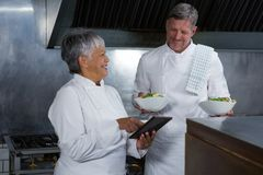 Male and female chef interacting with each other. In the kitchen Royalty Free Stock Photography