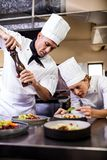 Male and female chefs preparing food in kitchen stock photos