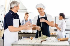Male And Female Chefs Preparing Pasta In Kitchen Stock Images