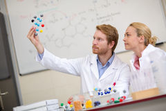 Male and female chemists studying molecular model in chemical cl. Chemists in classroom show molecular model and studying with his assistant Stock Photos