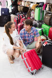 Male and female chooses suitcase Royalty Free Stock Photos
