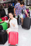 Male and female chooses suitcase. Happy male and female chooses suitcase at the store Stock Images