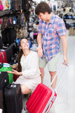Male and female chooses suitcase. Positive male and female chooses suitcase at the store Royalty Free Stock Images