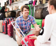 Male and female chooses suitcase. Smiling young male and female chooses suitcase at the store Royalty Free Stock Images